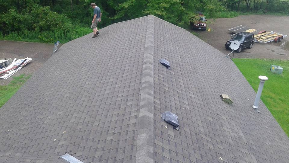 workers repairing roof on home